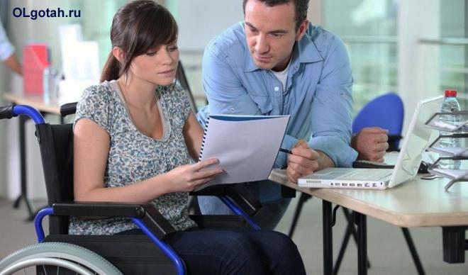 Девушка-инвалид читает документацию вместе с коллегой по работе