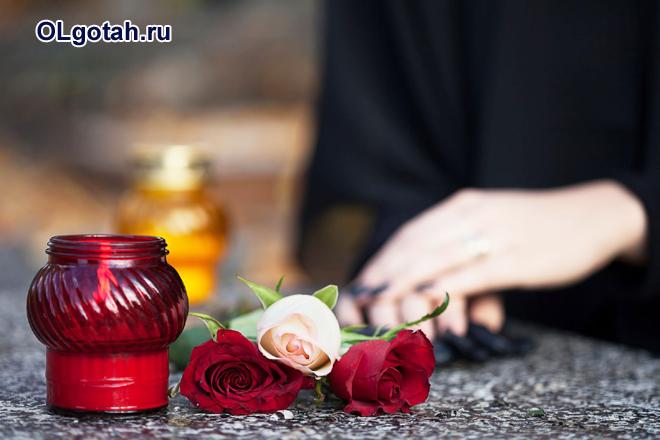 Женщина, потерявшая близкого человека, стоит рядом со цветами