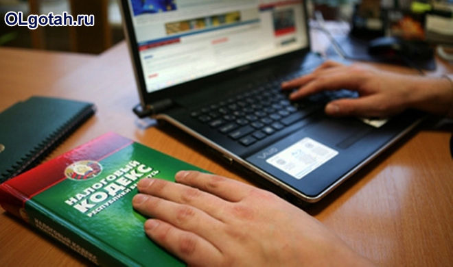 Мужчина работает за ноутбуком, рядом лежит налоговой кодекс