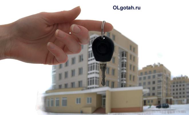 Человек держит в руке ключи от квартиры в многоэтажке