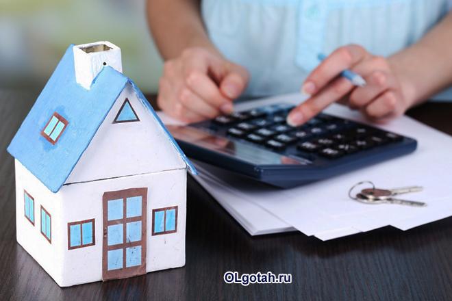 Девушка считает на калькуляторе, рядом стоит макет дома из картона
