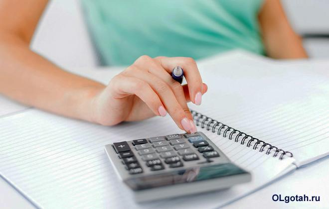 Девушка считает на калькуляторе цифры и записывает в тетрадь