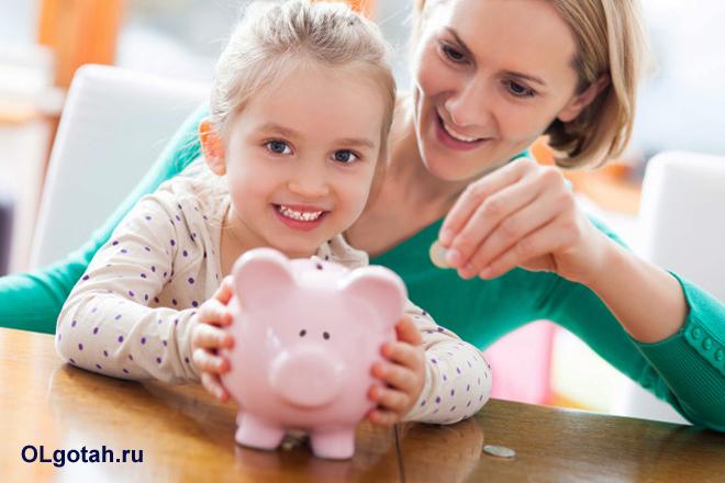 Мама и дочка откладывают денежку в копилку-хрюшку