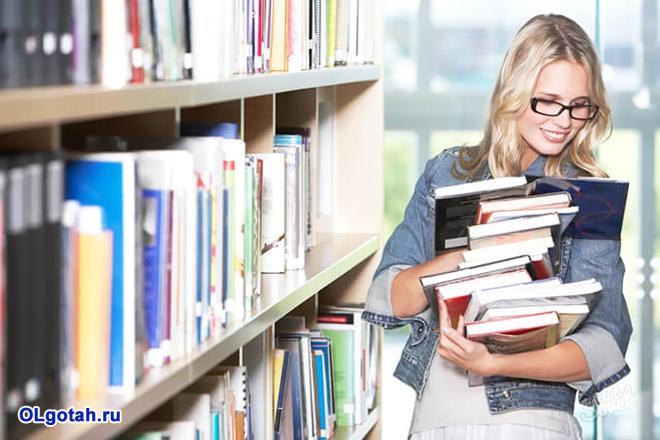 Девушка смотрит книги в библиотеке