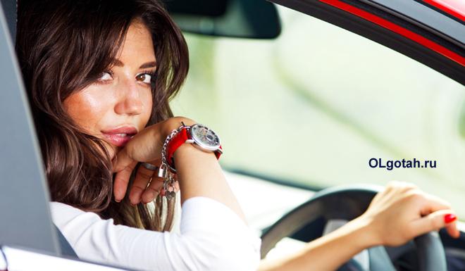 Красивая девушка за рулем красной машины