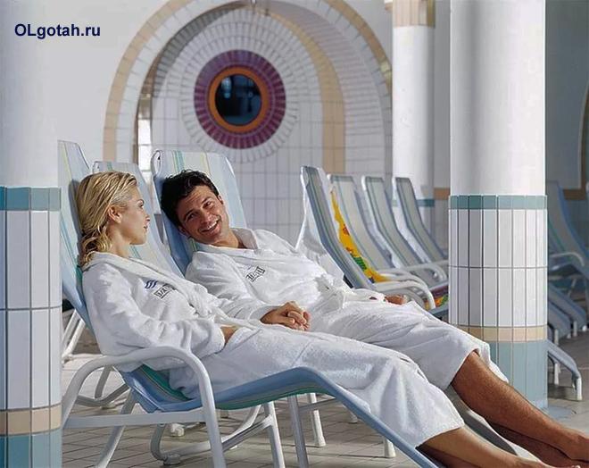 Мужчина и женщина в белых халатах отдыхают на шизлонгах