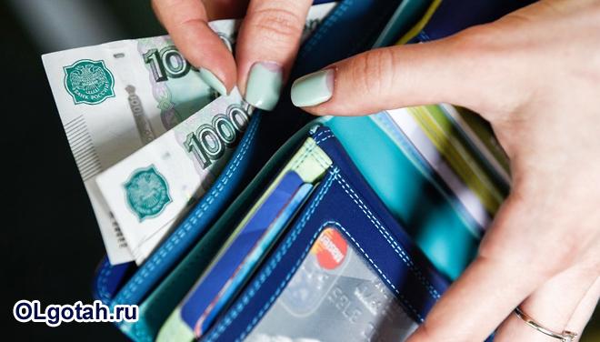 Девушка достает деньги из кошелька