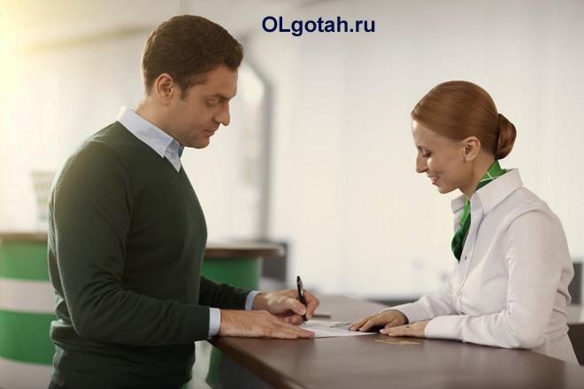 Мужчина подписывает документы в сбербанке