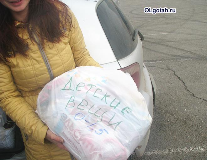 Девушка с пакетом детских вещей