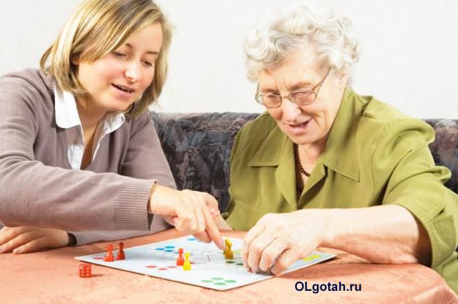 Девушка и пенсионерка играют в настольную игру