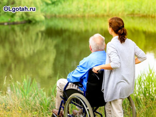 Девушка и пенсионер в инвалидном кресле на природе