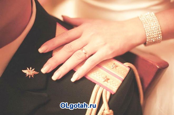 Девушка с красивым браслетом положила руку на погоны военного