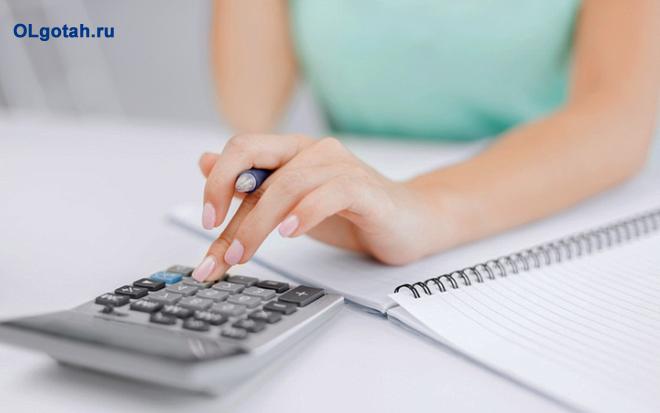 Девушка ведет расчеты на калькуляторе