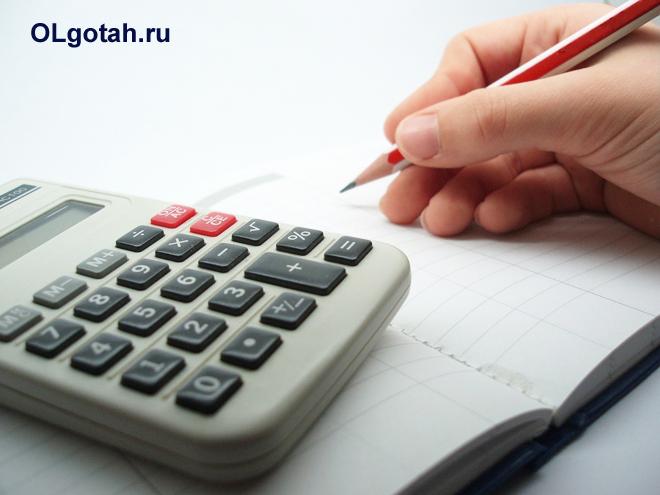 Человек делает в записной книжки записи карандашом, рядом лежит калькулятор