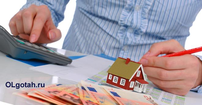 Бизнесмен пересчитывает на калькуляторе деньги за дом