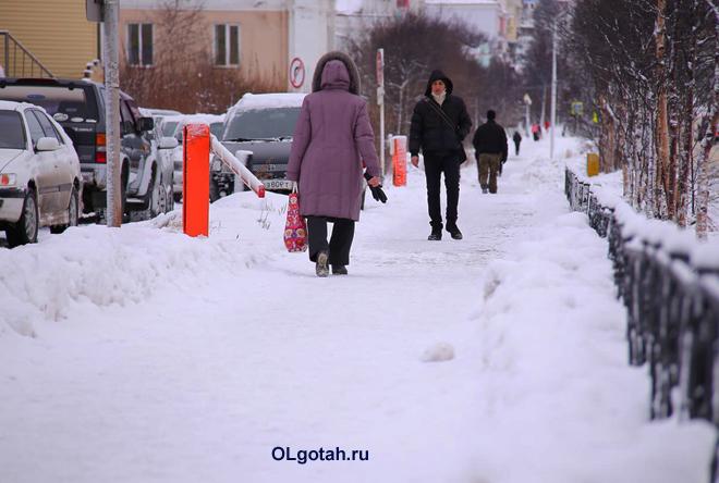 Прохожие идут по тротуару зимой