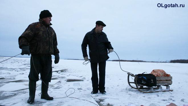 Мужчины везут санки по льду
