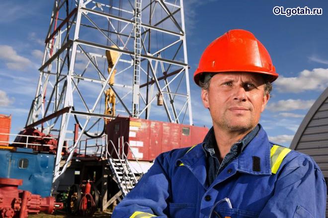 Рабочий в каске на фоне строительного крана