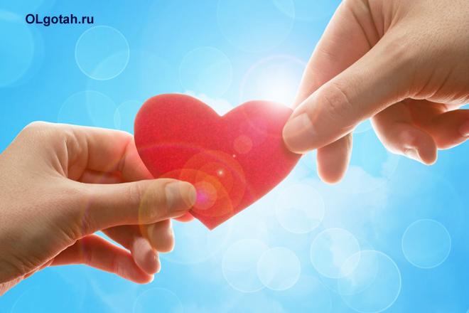 Человеческие руки держат картонное сердечко
