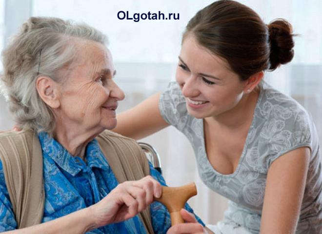 Социальный работник разговаривает с пенсионеркой