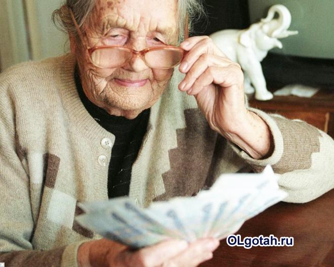 Пенсионерка смотрит на деньги