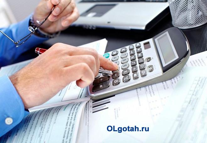 Офисный работник считает прибыль на калькуляторе