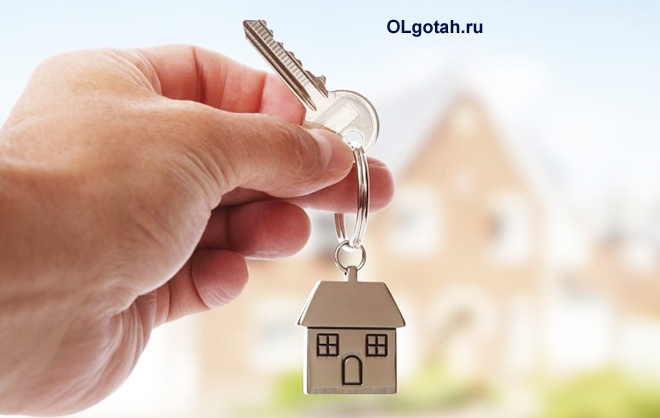 Человек держит ключи с брелком в виде домика