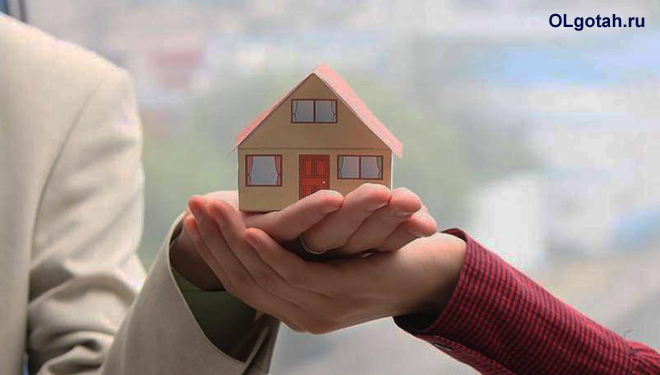 Женщина и мужчина держат вместе в руках игрушечный домик