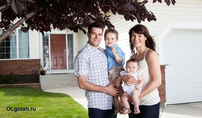 Семья с детьми стоит около дома