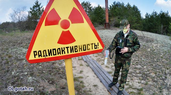 Военный в респираторе измеряет уровень радиации