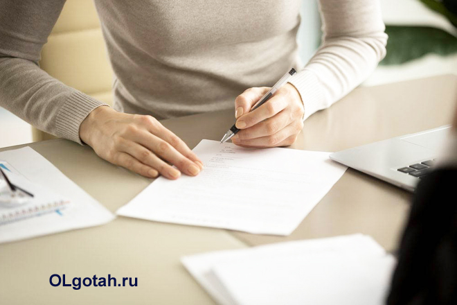 Девушка пишет заявление на листе бумаги