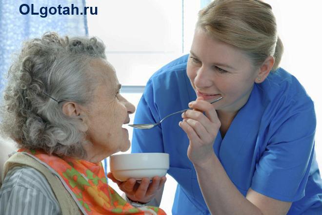 Девушка кормит бабушку с ложечки