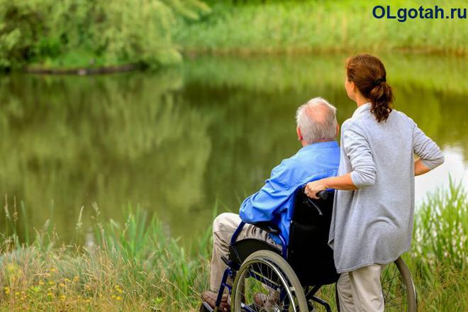 Девушка гуляет с дедушкой в инвалидном кресле на природе
