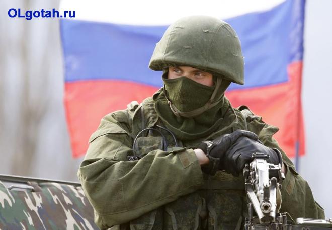 Военный в экипировке на фоне флага России